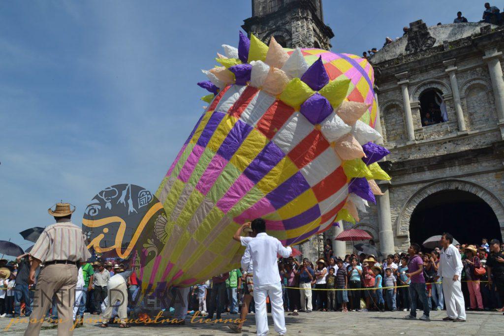 Monumentales globos multicolores son elevados con la ayuda de varias personas.